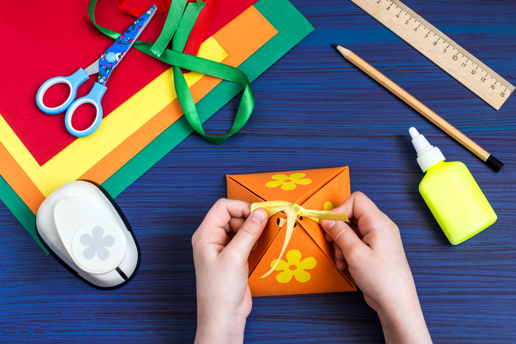Making a gift box by the child. Children's art project. DIY concept. Step-by-step photo instruction. Step 7. Child ties up a bow on the box
