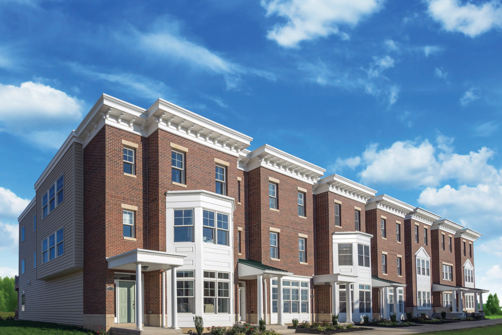 Exterior brick townhomes with bright blue cloudy sky.