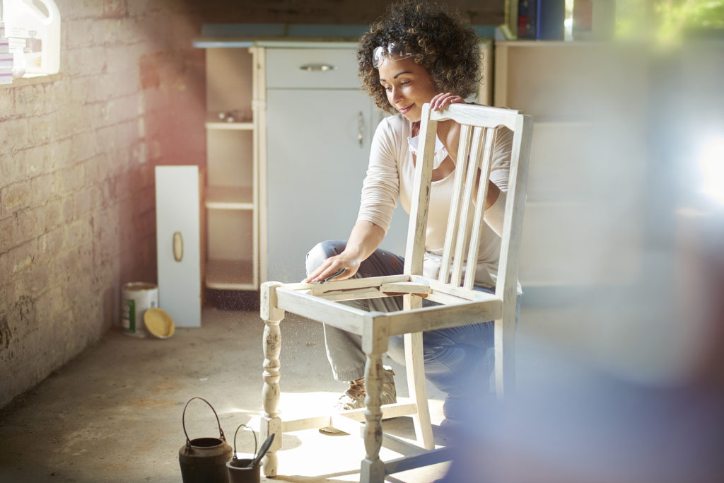 A woman restores and improves an old wooden chair in her workshop