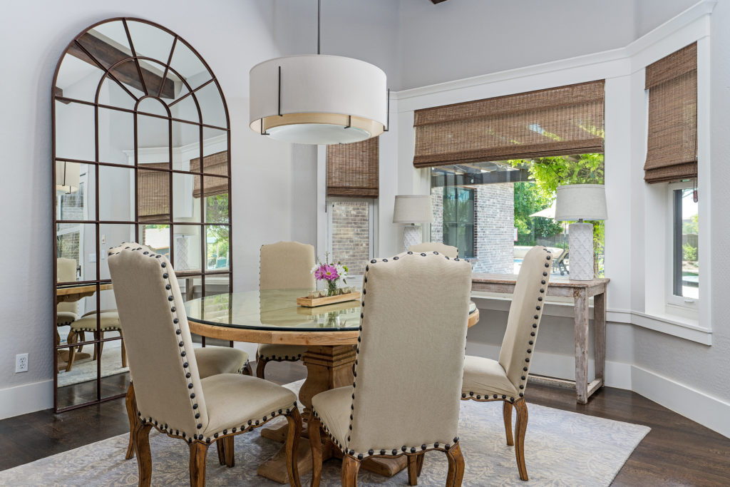 Modern dining room interior design with lots of natural lighting and huge farmhouse mirror.