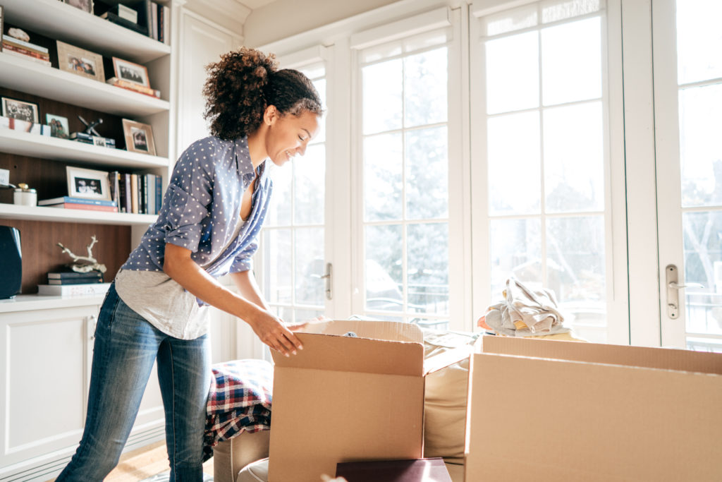 Woman packing up items before donating trying to organize her home.