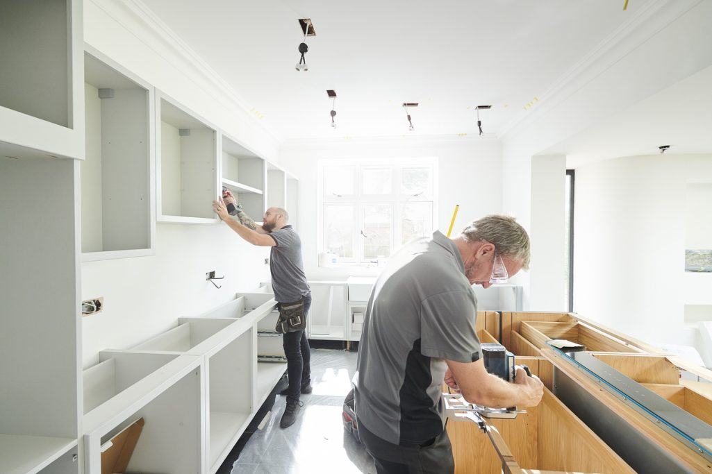 Joinery team fitting a new construction home kitchen