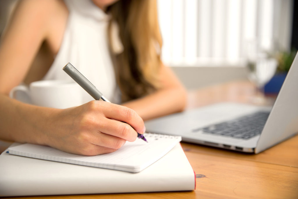 Woman writing new years resolutions on a notepad